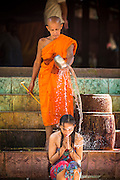 """02 JULY 2013 - ANGKOR WAT, SIEM REAP, SIEM REAP, CAMBODIA:  A Buddhist monk blesses a woman by splashing her with water at a small monastery near the Bayon temple in the Angkor Wat complex. Angkor Wat is the largest temple complex in the world. The temple was built by the Khmer King Suryavarman II in the early 12th century in Yasodharapura (present-day Angkor), the capital of the Khmer Empire, as his state temple and eventual mausoleum. Angkor Wat was dedicated to Vishnu. It is the best-preserved temple at the site, and has remained a religious centre since its foundation– first Hindu, then Buddhist. The temple is at the top of the high classical style of Khmer architecture. It is a symbol of Cambodia, appearing on the national flag, and it is the country's prime attraction for visitors. The temple is admired for the architecture, the extensive bas-reliefs, and for the numerous devatas adorning its walls. The modern name, Angkor Wat, means """"Temple City"""" or """"City of Temples"""" in Khmer; Angkor, meaning """"city"""" or """"capital city"""", is a vernacular form of the word nokor, which comes from the Sanskrit word nagara. Wat is the Khmer word for """"temple grounds"""", derived from the Pali word """"vatta."""" Prior to this time the temple was known as Preah Pisnulok, after the posthumous title of its founder. It is also the name of complex of temples, which includes Bayon and Preah Khan, in the vicinity. It is by far the most visited tourist attraction in Cambodia. More than half of all tourists to Cambodia visit Angkor.         PHOTO BY JACK KURTZ"""