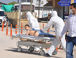 April 4, 2017 - Hatay, Hatay Province, Turkey - Men in masks and hazmat suits push a boy to the hospital on a gurney. The young victim, was a part of a supposed nerve gas attack (possibly the powerful and lethal sarin nerve gas) in north-western Syria. Death toll at 70 and rising, many childern. The airstrikes appear to have targeted clinics treating the wounded in Khan Sheikhoun, Idhib Province it is a rebel-held town of 165,000. Around 30 Turkish ambulances gathered at the border in Hatay Province for medical evacuation of victims after the Syrian toxic gas attack, to be brought to Turkey for immediate medical aid. (Credit Image: © Ferhat Dervisoglu/Depo Photos via ZUMA Wire)