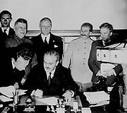 Soviet Foreign Commissar Vyacheslav Molotov signs the German-Soviet nonaggression pact; Joachim von Ribbentrop and Josef Stalin stand behind him. Moscow, August 23. 1939.World War II