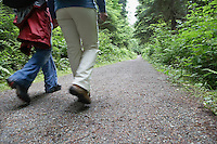 Two people walking on forest trail back view low section
