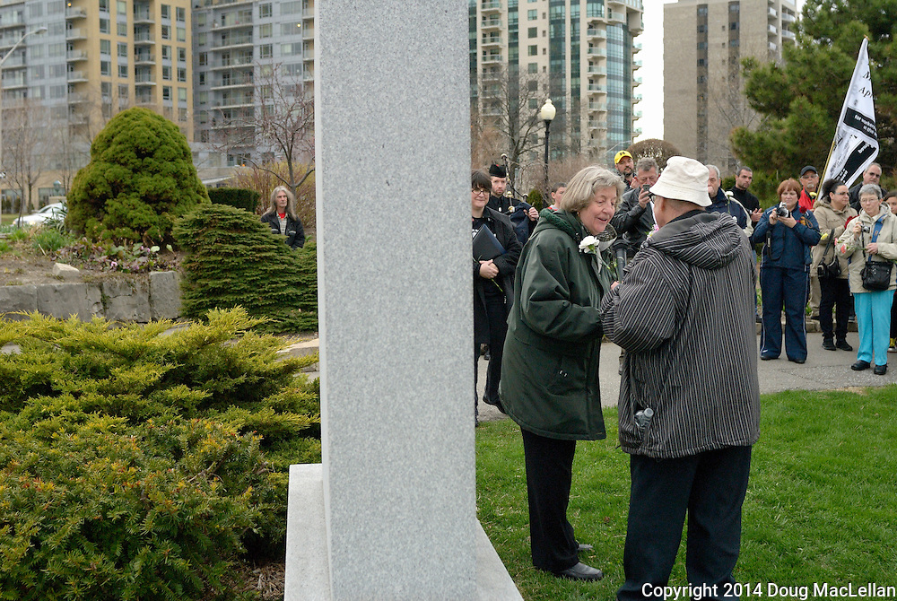 A priest thanks a speaker after her speech for Workers' National Day of Mourning at the wreath laying ceremony at Reaume Park.
