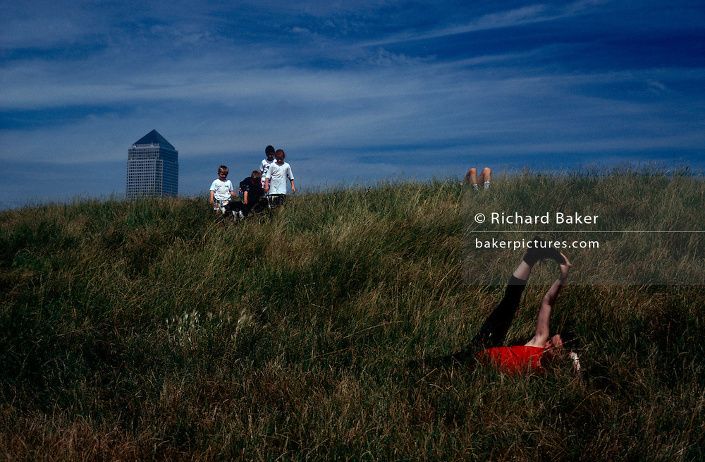 Near children playing with a goat and a man laying with just his knees showing, a woman exercises her hamstrings in long grass on an embankment near the tall Canary Wharf tower structure a mile away in the background at Dockland's area of East London. Above the grassy bank at Mudchute, a city farm on London's Isle of Dogs, England. It is a seemingly rural location but is, in fact, an area of inner-city London, close to major construction projects, transforming Docklands into a major centre for finance and new housing.