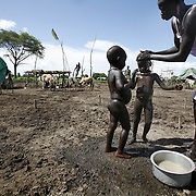 Dinka children get a bath at the family compound in cattle camp, amongst the mud, manure, and cattle urnie. Cows are Dinkaland's diamonds. They are exchanged upon marriage and handed out as prized gifts. They stand for beauty, status and wealth, and the Dinka are so devoted to them, that they would rather live off milk (with a little sorghum here and there) than steak.