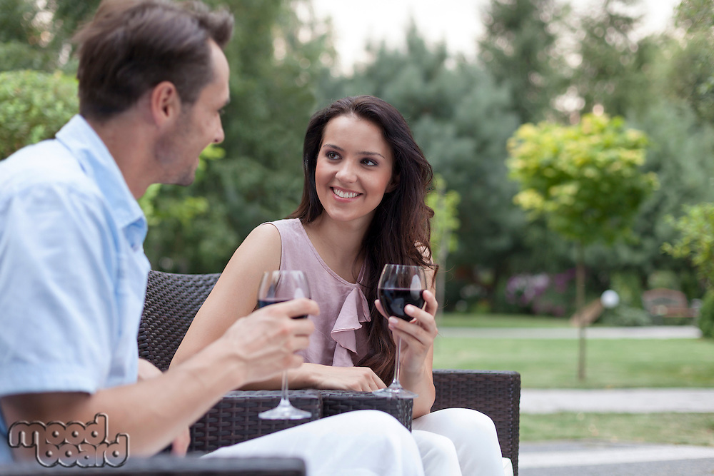 Happy young couple having red wine on chairs in park