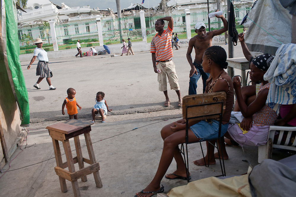 A family sits next to their makeshift tent, which is located directly in front of the destroyed National Palace, on July 9, 2010 in Port-au-Prince, Haiti.
