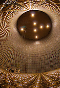 The Surreal World of Neutrino Detectors<br /> <br /> Neutrinos are one of the fundamental particles which make up the universe, but not in the way electrons, protons and neutrons are. These particles are extremely tiny, nearly massless and electrically neutral so they are not affected by electromagnetic forces and react very weakly with other particles of nature. Neutrinos are produced by the decay of radioactive elements in nuclear reactions such as in the core of the sun or exploding stars. Once born, they travel in straight lines at the speed of light passing through solid matter almost entirely unhindered. Although tiny, they carry a colossal amount of energy — some of these carry the same amount of energy as a well hit tennis ball. To detect these particles using the same technology they use at the Large Hadron Collider in Switzerland, one would require a ring of magnets the size of Earth's orbit around the Sun.<br /> Neutrino detectors therefore use entirely different kind of science and technology. Some detectors use large tanks filled with water and surrounded by photomultiplier tubes that watch for radiation emitted when an incoming neutrino creates an electron or muon in the water. Other detectors have tanks filled with chlorine or gallium or other liquids. Neutrino detectors are often built underground, to isolate the detector from cosmic rays and other background radiation.<br /> <br /> <br /> The Super-Kamiokande neutrino detector is located 1,000 meters under Mount Kamioka near the city of Hida, in Japan. The detector consist of a cylindrical stainless steel tank 41 meters by 39 meters holding 50,000 tons of ultra-pure water and surrounded by more than 11,000 photomultiplier tubes (PMT). It is one of the largest detector of its kind.<br /> When a passing neutrino interacts with the electrons or nuclei of water, it can produce a charged particle that moves faster than the speed of light in water. This creates a cone of light known as Cherenkov radiation