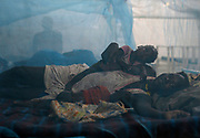 A woman rests in bed with her children in the paediatric ward at the Medecins Sans Frontieres (MSF) hospital inside the United Nations Mission in South Sudan (UNMISS) base, Bentiu, Rubkona County, South Sudan.