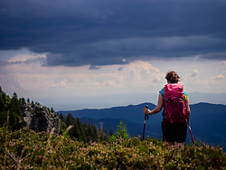 Women hiker standing above mountains towards valley at Col de la Schlucht in Vosges, Alsace, France