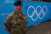 A portrait of a Lance Corporal in the Rifles regiment of the British army next to the Olympic rings logo before the start of the canoe slalom heats at the Lee Valley White Water Centre, north east London, on day 3 of the London 2012 Olympic Games. A total of 18,000 defence personel were called upon to make the Games secure following the failure by security contractor G4S to provide enough private guards. The extra personnel have been drafted in amid continuing fears that the private security contractor's handling of the £284m contract remains a risk to the Games.