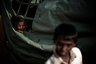A child displaced by the war between the government of Sri Lanka and the LTTE looks out from a tent in a camp for internally displaced people at the Menick farm near Vavuniya, Sri Lanka on July 8, 2009. Nearly 300,000 people remain in camps after the war as the government works on resettling them and screening for remaining LTTE members.