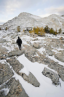 A person in black clothing standing in the upper Enchantments below Little Annapurna, Enchantment Lakes Wilderness Area, Washington Cascades, USA.