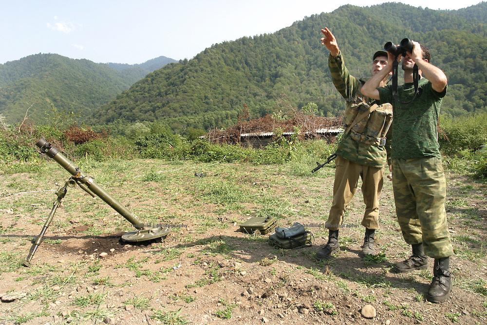 Georgien/Abchasien, Suchumi, 2006-08-28, Abchasische Soldaten beobachten mit einem Fernglas die Umgebung im Kodorital. Neben ihnen ein Mörser. Abchasische Soldaten im zwischen Abchasen und Georgiern umkämpften Kodorital . Abchasien erklärte sich 1992 unabhängig von Georgien. Nach einem einjährigen blutigen Krieg zwischen den Abchasen und Georgiern besteht seit 1994 ein brüchiger Waffenstillstand, der von einer UNO-Beobachtermission unter personeller Beteiligung Deutschlands überwacht wird. Trotzdem gibt es, vor allem im Kodorital immer wieder bewaffnete Auseinandersetzungen zwischen den Armeen der Länder sowie irregulären Kämpfern. (Abkhazian soldiers observing the surrounding in the Kodori gorge, where abkhazian and georgian fighting each other. Near by a mortar. Abkhazia declared itself independent from Georgia in 1992. After a bloody civil war a UNO mission observing the ceasefire line between Georgia and Abkhazia since 1994. Nevertheless nearly every day armed incidents take place in the Kodori gorge between the both armys and unregular fighters )
