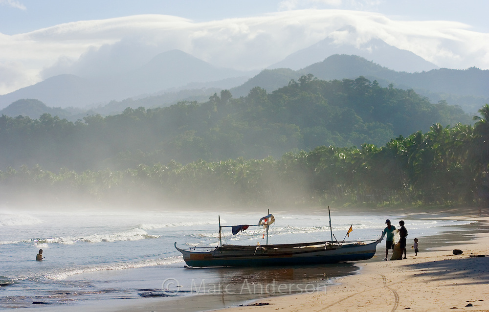 People standing next to a boat on a beach with mountains in the background, Sabang, Palawan, Philippines.