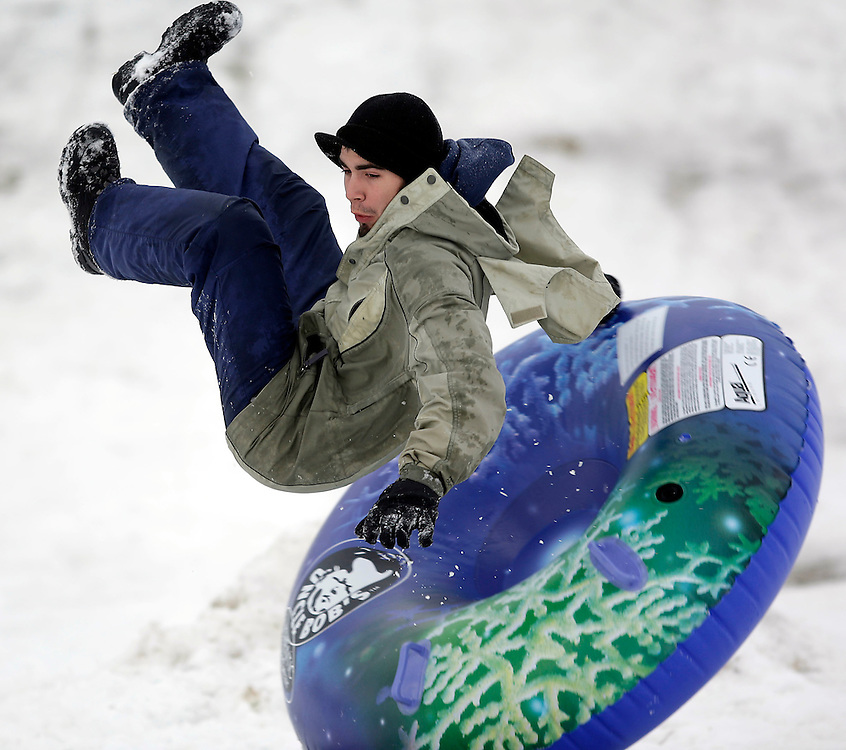 CAPTION ONLY WEATHER FEATURE--Chris Hammel of Roy, Utah takes advantage of newly fallen snow to slide down the hill in a park just north of Shriners Hospital in Salt Lake City, Utah Saturday, Jan. 5, 2007.  August Miller/ Deseret Morning News .
