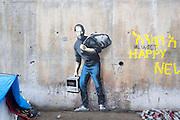 FRANCE, Calais: 18 December 2015 The Banksy painting of Steve Jobs in the refugee camp known as 'The Jungle'. A refugee from Sudan now charges €1 to take a picture of the art work. The camp in Calais is now believed to hold 7,000 refugees, who are all trying to prepare for the cold winter months ahead.<br /> Rick Findler / Story Picture Agency
