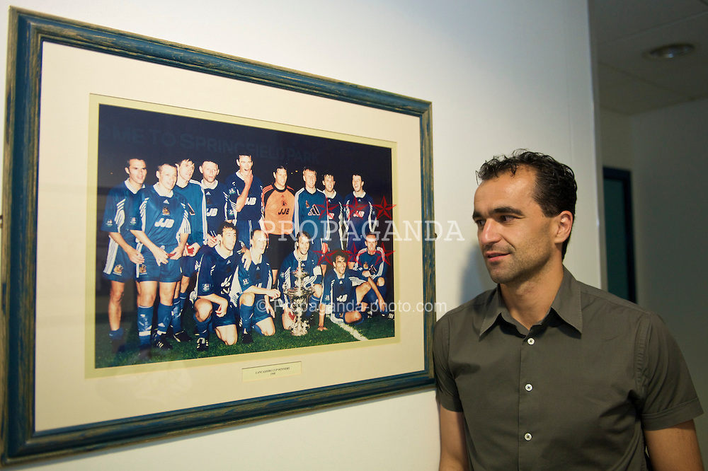 WIGAN, ENGLAND - Monday, August 24, 2009: Wigan Athletic's manager Roberto Martinez stands next to a team photograph from the club's Lancashire Cup victory in 1998. (Photo by David Rawcliffe/Propaganda)
