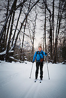 A woman cross-country skiing on a groomed trail in the early evening.  mazama, Washington, USA.