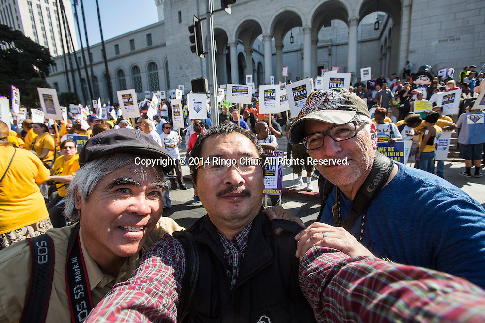 (L to R) Photographers Nick Ut, Ringo Chiu, and Ted Soqui shoot the labor rally in downtown Los Angeles Tuesday, October. 28, 2014. (Photo by Ringo Chiu/PHOTOFORMULA.com)