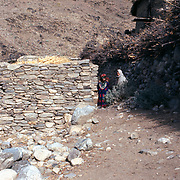 2-4 December 1976<br /> From here to District Dawlat Shah all are Pashai. The Alishang Woleswali is mixed Pushtun and Pashai.<br /> Closed door in stone wall. Two girls to right emerging from lane: girl on left dressed in red wears elaborate silver jewelry; girl on right a white chadder. Also observed metal ornaments on hats and yokes of dresses and necklace collars made of tiny beads.