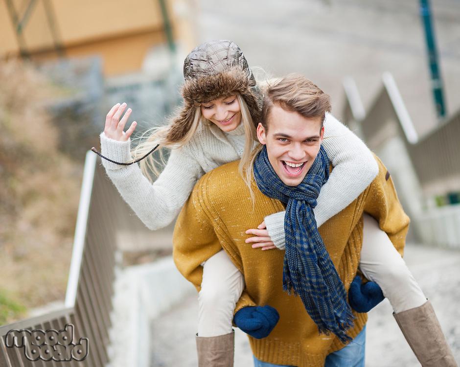 Portrait of cheerful man piggybacking woman on stairway