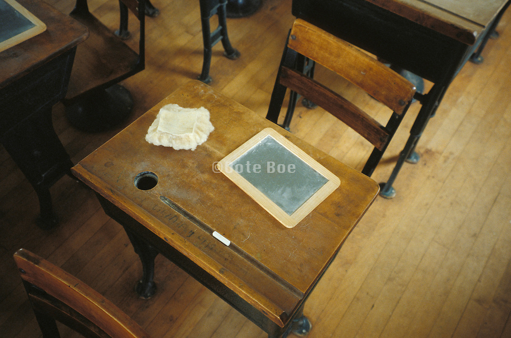 slate chalk and eraser on old fashioned classroom desk