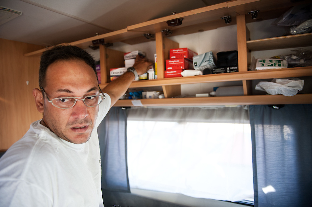 MSF doctor Dimitris Giannousis  checking the medicine cabinet of the camper van of MSF at Mytiline port, Lesvos, Greece.