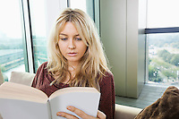 Close-up of relaxed young woman reading book in living room at home