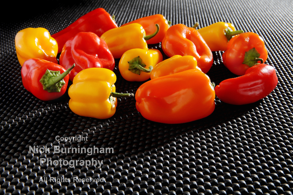 Red, Orange and Yellow Mini Bell Peppers with dramatic diagonal lighting on a black textured surface with copy space below.