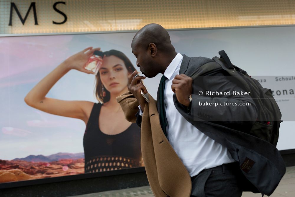 A man rushes past a billboard ad featuring the face of a model advertising a perfume outside the retailer Debenhams on Oxford Street, on 16th April 2018, in London, England.