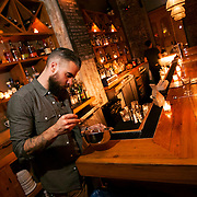 """November 18, 2013 - New York, NY : Bartender Maks Pazuniak works with a whisk as he makes his winter-warming cocktail, the """"Bitter Coffee,"""" at The Counting Room on Berry Street in Williamsburg in Brooklyn on Monday evening.  The drink is comprised of Cynar, dark rum, maple syrup, an egg yolk, vanilla, coffee, and a grating of nutmeg.  CREDIT: Karsten Moran for The New York Times"""
