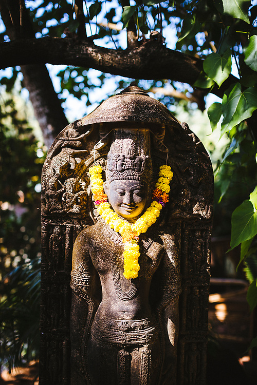 A religious statue with a flower garland at the Ashiyana Yoga Retreat in Goa, India.