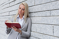 Beautiful young businesswoman reading notes in organizer while leaning on wall