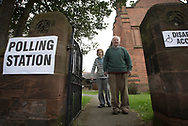 Voters leaving a polling station in Hoylake, Wirral to cast their votes at the 2015 UK General Election. They were voting in the marginal Wirral West constituency, held since the 2010 election by Esther McVey MP for the Conservative Party. Voters went to the polls across the UK on 7th May to elect 659 member of parliament.
