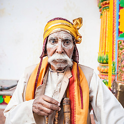 Old man in a temple during holi celebration, Mathura, India, Asia.