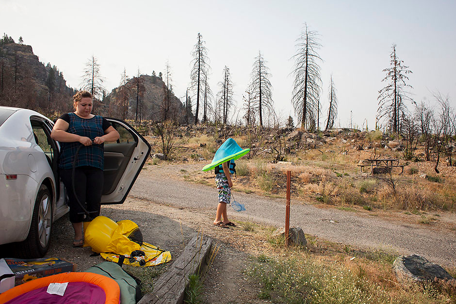 Sofia Onishenko, left, prepares to swim with her nephew, Elijah Orekhov, right, while camping at Alta Lake State Park, which was damaged by the Carlton Complex fire, in Pateros, Washington on July 9, 2015.