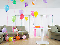 Young girl (7-9) sitting in living room full of balloons