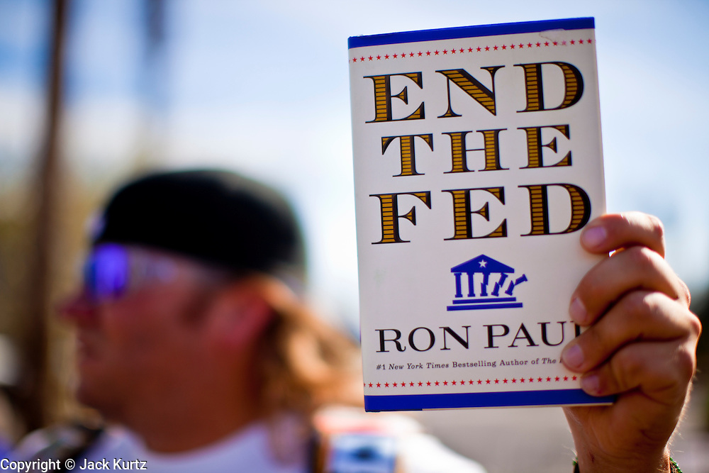 "22 FEBRUARY 2012 - MESA, AZ: CHAD GEESE, from Scottsdale, AZ, rallies in support of Congressman Ron Paul in Mesa, Wednesday. Geese held up a copy of Paul's book ""End the Fed,"" which has also become the rallying cry of the Paul campaign. Ron Paul supporters had hundreds of people in front of the Mesa Arts Center before CNN's Arizona Republican Presidential Debate Wednesday.     PHOTO BY JACK KURTZ"