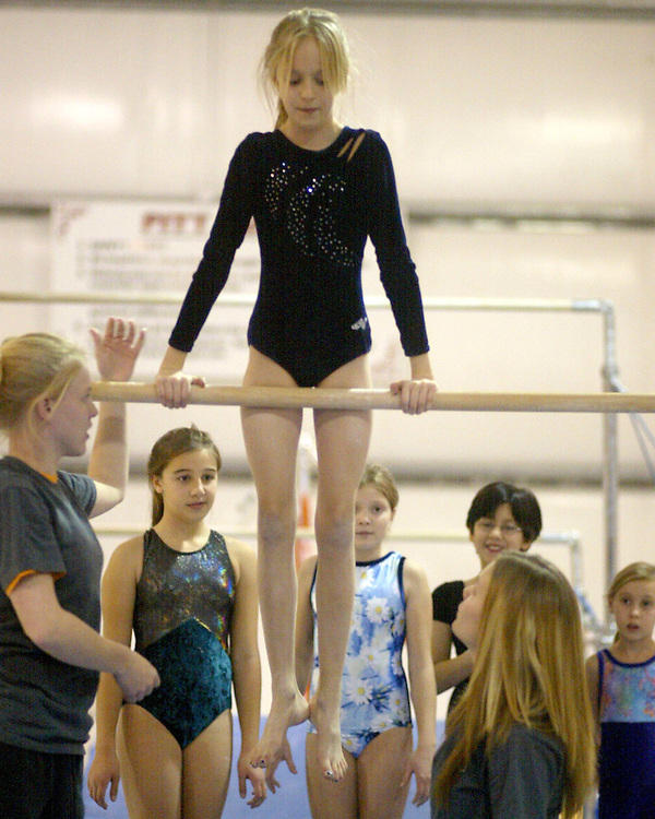 Hannah Billstone (L) and Emily Storms(R) help Marishka Fadale on the uneven bars at the Lakewood Y 12.4 photo by Mark L. Anderson