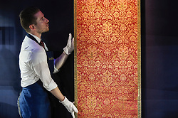 "© Licensed to London News Pictures. 18/10/2019. LONDON, UK. A technician presents a ""A rare and important Ottoman silk and metal-thread brocade panel (Kemha)"", Turkey, probably Bursa, early 17th century (Est. GBP60,000-80,000).  Preview of Islamic, Indian and Middle Eastern art to be auctioned at Sotheby's, New Bond Street, on 22 and 23 October.  Photo credit: Stephen Chung/LNP"