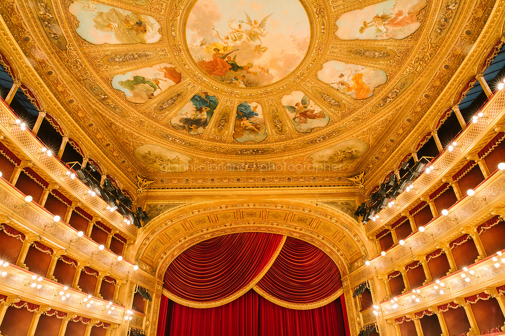PALERMO, ITALY - 18 FEBRUARY 2018: A view of the auditorium, the stage and the the wheel overlooking the auditorium (which looks like a giant flower with eleven petals that, thorough a system of ropes, can open up to let the hot air out and ventilate the room) are seen here from the Royal Box at the Teatro Massimo in Palermo, Italy, on February 18th 2018.<br /> <br /> The Teatro Massimo Vittorio Emanuele is an opera house and opera company located  in Palermo, Sicily. It was dedicated to King Victor Emanuel II. It is the biggest in Italy, and one of the largest of Europe (the third after the Op&eacute;ra National de Paris and the K. K. Hof-Opernhaus in Vienna), renowned for its perfect acoustics. It was inaugurated in 1897.