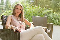 Portrait of beautiful young woman relaxing on chair in park