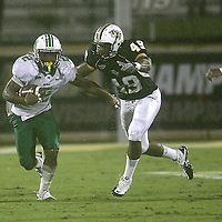 Marshall running back Tron Martinez (2) runs past Central Florida defensive lineman Cam Henderson (49) during an NCAA football game between the Marshall Thundering Herd and the Central Florida Knights at Bright House Networks Stadium on Saturday, October 8, 2011 in Orlando, Florida. (Photo/Alex Menendez)
