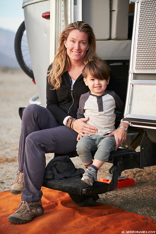 A mother and son camping in the desert with an Airstream RV.