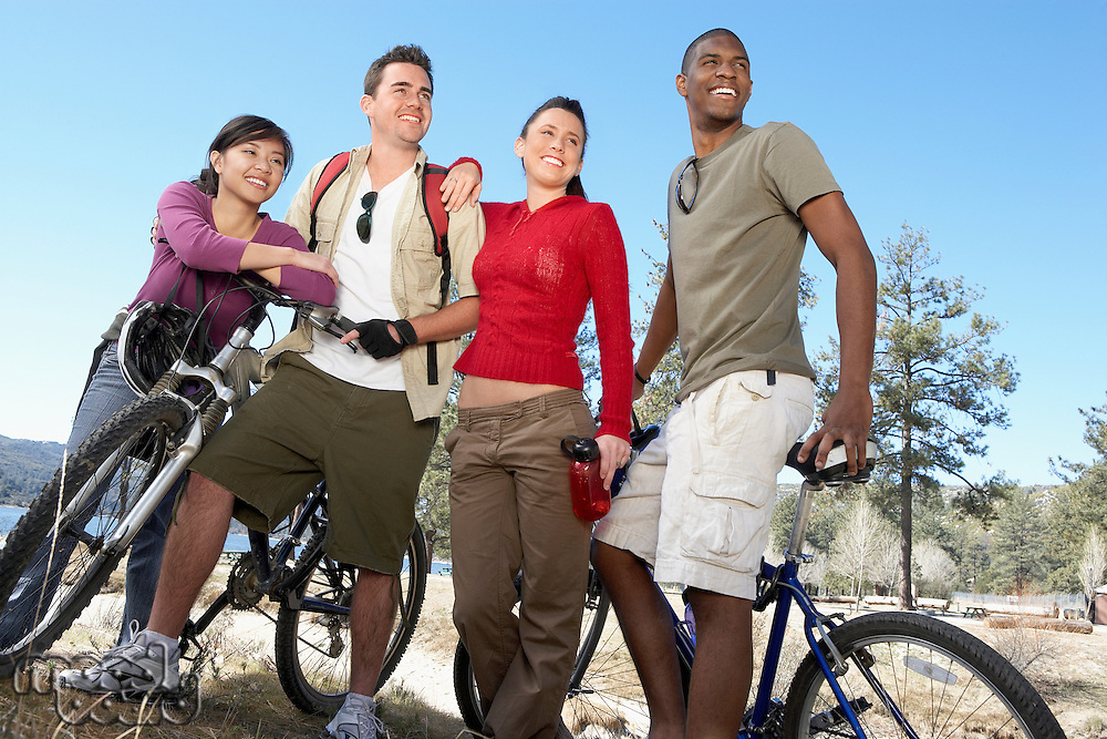 Four young adults standing by lake shore with mountain bikes.