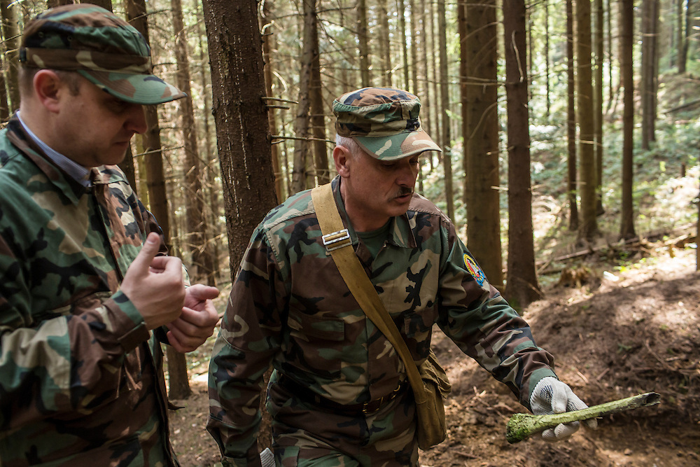 SKOLE, UKRAINE - MAY 1, 2015: Svyatoslav Sheremeta, left, and Volodymyr Kharchuk, holding a human tibia, director and deputy director of the organization Dolya, respectively, visit the site of a World War II-era mass grave believed to contain the remains of Ukrainian partisans where the bone was found, along with others, in Skole, Ukraine. Dolya was formed to excavate and repatriate remains from World War II, though its focus is often on locating the graves of Ukrainian partisans killed by Soviet forces. CREDIT: Brendan Hoffman for The New York Times