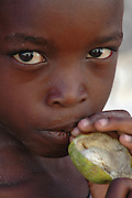 A portrait of a young boy enjoying a piece of fruit on the island of Ilha De Mocambique, Mozambique, Southern East Africa.