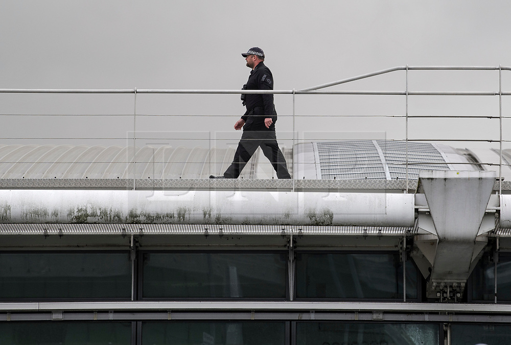 © Licensed to London News Pictures. 12/09/2019. London, UK. A police officer patrols the roof of Terminal 5 at Heathrow Airport in West London where activists from Heathrow Pause, a splinter of the environmental protest group Extinction Rebellion, are planning to fly toy drones early tomorrow morning in an attempt to cause disruption. Photo credit: Ben Cawthra/LNP