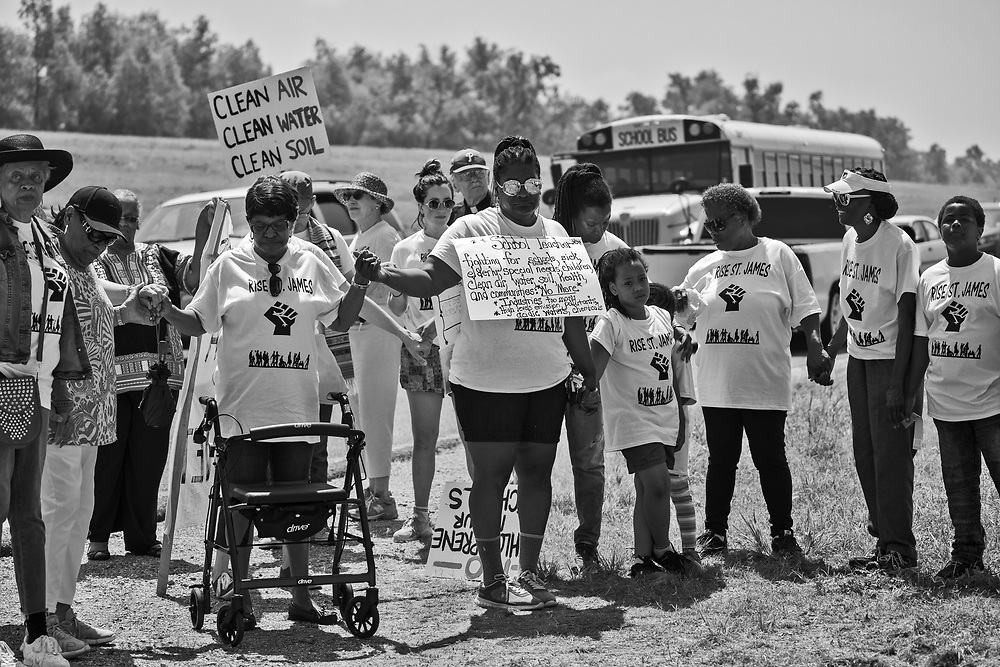 """Marchers in St. James Louisaina on the third day of a five day march through Louisiana's 'Cancer Alley' held by the Coalition Against Death Alley pray at the site of Formosa's proposed plant. The Coalition Against Death Alley (CADA), is a group of Louisiana-based residents and members of various local and state organizations, is calling for a stop to the construction of new petrochemical plants and the passing of stricter regulations on existing industry in the area that include the groups RISE St. James, Justice and Beyond, the Louisiana Bucket Brigade, 350 New Orleans, and the Concerned Citizens of St. John  Louisiana's Cancer Alley, an 80-mile stretch along the Mississippi River, is also known as the """"Petrochemical Corridor,"""" where there are over 100 petrochemical plants and refineries"""