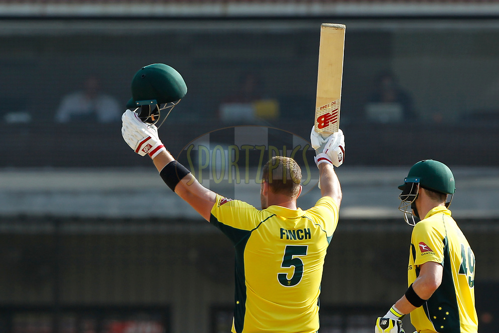 Aaron Finch of Australia raises his bat after scoring 100 runs during the 3rd One Day International between India and Australia held at the Holkar Stadium in Indore on the 24th  September 2017<br /> <br /> Photo by Deepak Malik / BCCI / SPORTZPICS