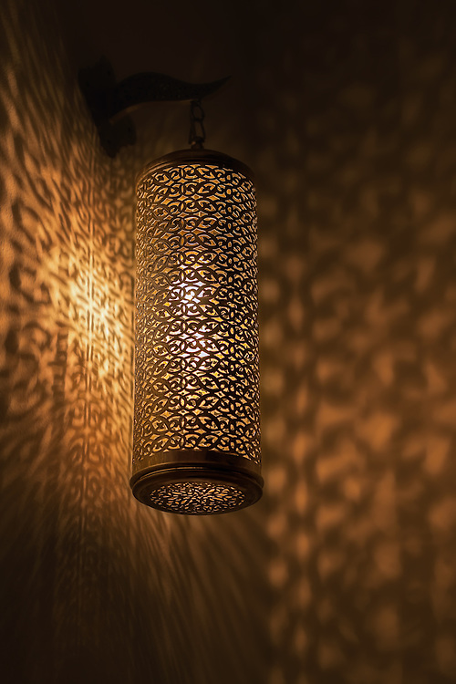 Lit moroccan brass lamp casting beautiful shadows on the wall.